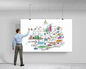 Image of businessman drawing business plan on white banner